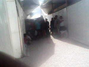 Detainees stand in the shade at a family camp, Nauru. There is no air conditioning, and some reports have suggested that the temp can reach up to 50 degrees in the tents. Image source: The Guardian